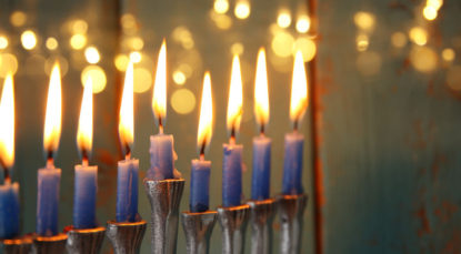 87742317 - low key image of jewish holiday hanukkah background with menorah (traditional candelabra) and burning candles